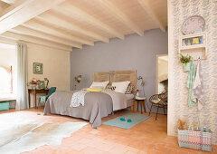 Schlafzimmer in Pastelltönen mit Doppelbett und Holzbalkendecke in französischem Landhaus