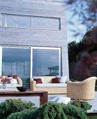 Holzterrasse mit gemütlichen Rattanmöbeln vor holzverkleidetem Fassadenausschnitt