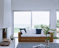 Wicker couch with white seat cushions and scatter cushions in front of sliding terrace doors with sea view