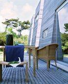 Holzterrasse mit Rattanmöbeln vor modernen Holzfassaden