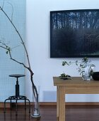 Oak table and retro swivel stool next to branches in glass vase