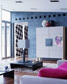 Designer cupboard with felt-covered doors against blue-grey wall, low table on flokati rug, table lamps and hot-pink cushions