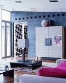 Designer-Schrank mit Filz an blaugrauer Wand davor Flokati mit Bodentisch, Tischleuchte und pinkfarbenen Kissen