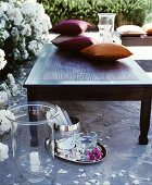 Cushions on coffee table in front of white-flowering rose bushes with candle lantern and silver tray on stone floor