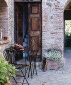 Delicate, folding, metal outdoor furniture outside traditional Mediterranean front door