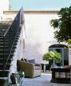 Rattan armchair in traditional Mediterranean courtyard with external staircase to one side