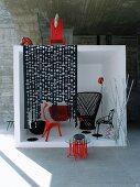 Schwarze und rote Designermöbel in weißem Kubus vor Betonwand