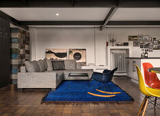 Grey sofa on blue rug in open-plan industrial-style interior