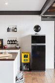 Black fridge against white wall in kitchen