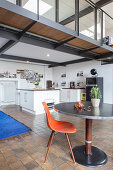 Dining table and designer chair in front of open-plan kitchen below mezzanine