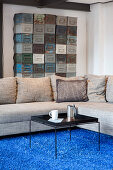Black coffee table and grey sofa on blue rug