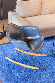 Blue designer rocking chair on bright blue rug