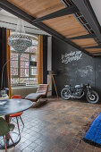 Motorbike in loft apartment with chalkboard wall and brown floor tiles