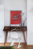 White designer chair at wooden desk with red artwork