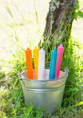 Colourful candles in zinc bucket
