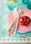 Strawberry tart and spoon on stack of colourful plates