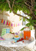 Snacks and drinks dispenser on garden table in front of garland of hand-made tassels on wall
