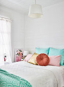 Colourful cushions on bed in bedroom with board wall