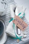 Stoffserviette mit Besteck und Platzkarte