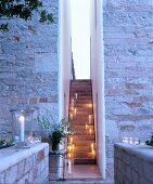 Narrow external staircase illuminated by candle lanterns