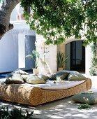 Gemütliche Korbliege mit Kissen im Schatten unter einem Baum