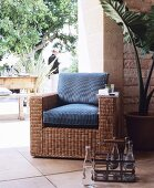 Rattan armchair with cushions on Mediterranean terrace