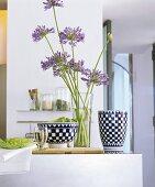Schmucklilien in der Vase neben Keramik mit Schachbrettmuster