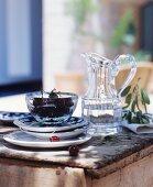 Wasserkrug und Schale mit Kirschen auf einem rustikalen Holztisch