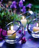 Brennende Kerzen in Glasschalen mit schräger Öffnung als stimmungsvolle Tischdekoration