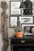 Feminine wooden sculpture next to Buddha statue on console table and black-framed photos and quotes on wall