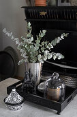 Black and white china pot next to silver vase on wooden tray