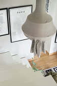 Pendant lamp and white staircase leading into living room