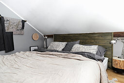 Double bed in attic room with rustic elements