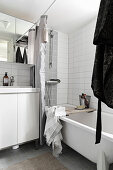 Washstand and bathtub in bathroom with pale tiles