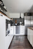 Stainless steel fridge in white fitted kitchen