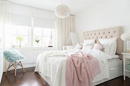 Doppelbett mit Betthaupt im Schlafzimmer in weißen und hellen Pastelltönen
