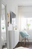 Schmaler, weißer Wandschrank mit Tischlampe, darüber Wandfernseher, Klassikerstuhl in Zimmerecke vor Fenster