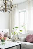 weiße Polstergarnitur und Beistelltisch mit Zimmerpflanze vor Fenster, im Vordergrund Couchtisch mit Rosenstrauß
