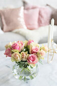 Spherical vase of roses and candelabra on coffee table in front of sofa with scatter cushions