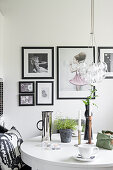 Black-framed pictures above round dining table