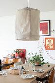 Große Deckenleuchte mit beigem Stoffschirm über gedecktem Tisch