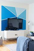 Bemalte Wand in verschiedenen Blautönen hinter dem Fernseher