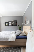Bed with wooden headboard in bedroom with grey walls