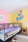 Metallbett vor zweifarbig gestrichener Wand im Kinderzimmer