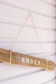 Schild aus einem alten Stück Holz an einer weißen Bretterwand