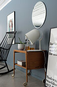 Retro wooden trolley below round mirror on grey wall