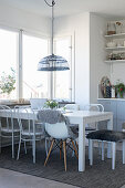 Dining table and various chairs in bright kitchen-dining room