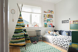 Hand-made teepee in child's bedroom in shades of green