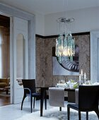 Set dining table below modern glass ceiling lamp