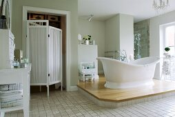 Free-standing bathtub on platform in vintage-style bathroom